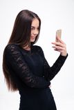 Mujer en vestido negro usando smartphone Fotos de archivo libres de regalías