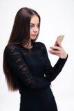 Mujer en vestido negro usando smartphone Foto de archivo