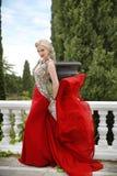 Mujer en vestido que agita rojo Modelo rubio de la moda en el vestido que sopla o foto de archivo