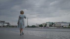 Mujer en vestido que camina en orilla del mar almacen de metraje de vídeo
