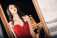 Mujer en vestido rojo antes del espejo Fotos de archivo