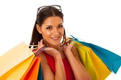 Mujer en vestido rojo con los panieres emocionados de compra en el mal Foto de archivo libre de regalías