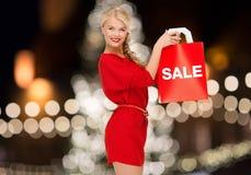 Mujer en vestido rojo con venta de la palabra en el panier Fotografía de archivo