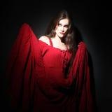 Mujer en vestido rojo en oscuridad Fotografía de archivo libre de regalías