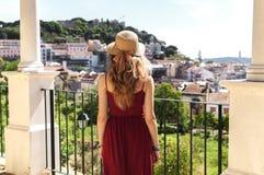 Mujer en vestido, sombrero del sol y lookimg rojos del bolso azul en la opinión im Lisboa Alfama, Portugal del panorama Fotos de archivo