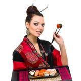 Mujer en vestido tradicional con la comida del este Foto de archivo