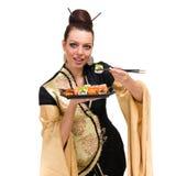 Mujer en vestido tradicional con la comida del este Foto de archivo libre de regalías
