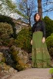 Mujer en vestido victoriano en el parque con la cascada fotografía de archivo