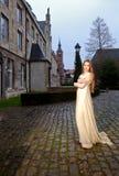 Mujer en vestido victoriano en un viejo cuadrado de ciudad por la tarde en perfil imagenes de archivo