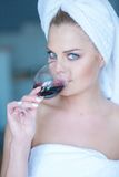 Mujer en vidrio de consumición de la toalla de baño de vino rojo Fotos de archivo libres de regalías