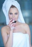 Mujer en vidrio que sorbe de la toalla de baño de vino rojo Imagen de archivo libre de regalías