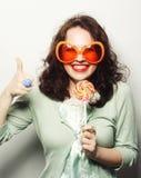 mujer en vidrios anaranjados grandes que lame la piruleta con su lengua Imágenes de archivo libres de regalías