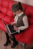 Mujer en vidrios con la computadora portátil en el sofá rojo Foto de archivo