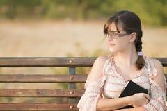 Mujer en vidrios con un libro en un banco Imagen de archivo