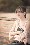 Mujer en vidrios con un libro en un banco Foto de archivo libre de regalías