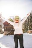 Mujer en vidrios divertidos de una Navidad delante de una casa de la montaña Imagenes de archivo