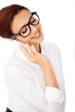 Mujer en vidrios que charla en un móvil Imagenes de archivo