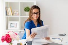 Mujer en vidrios que lee el periódico en la oficina Fotos de archivo libres de regalías
