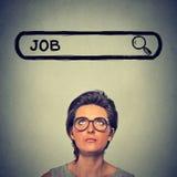 Mujer en vidrios que piensa buscando un nuevo trabajo aislada en fondo gris de la pared imagenes de archivo