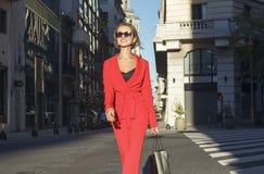 Mujer en vidrios rojos del traje y de sol que camina en la calle Fotografía de archivo
