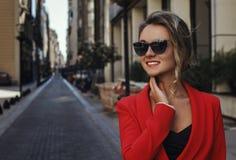 Mujer en vidrios rojos del traje y de sol que sonríe al aire libre Imágenes de archivo libres de regalías