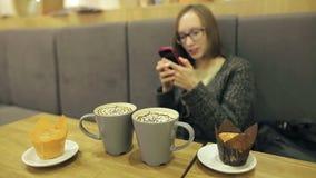Mujer en vidrios usando el app en smartphone en café de consumición del coco del café que sonríe y que manda un SMS en el teléfon almacen de video