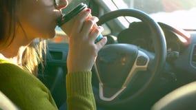 Mujer en vidrios usando un smartphone y café de las bebidas en el coche almacen de video
