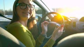 Mujer en vidrios usando un smartphone y hablar con alguien en el coche almacen de metraje de vídeo