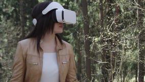 Mujer en visualizador en forma de visor en el bosque almacen de video