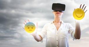 Mujer en VR con la red y emojis con las llamaradas contra el cielo nublado Foto de archivo libre de regalías