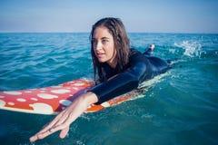 mujer en wetsuit con una tabla hawaiana en un día soleado Imagen de archivo
