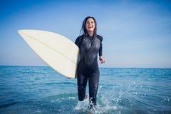 mujer en wetsuit con una tabla hawaiana en un día soleado Foto de archivo