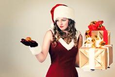 Mujer en y sombrero de Santa con un regalo Imágenes de archivo libres de regalías