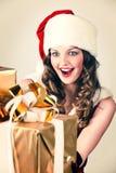 Mujer en y sombrero de Santa con un regalo Foto de archivo