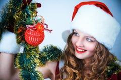 Mujer en y sombrero de Santa con una bola de la Navidad Fotografía de archivo libre de regalías