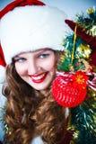 Mujer en y sombrero de Santa con una bola de la Navidad Imágenes de archivo libres de regalías