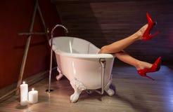 Mujer en zapatos rojos del tacón alto en baño Foto de archivo