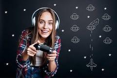 Mujer encantada alegre que juega a los videojuegos Imágenes de archivo libres de regalías