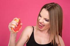Mujer encantada bonita que exprime el jugo de pomelo por las manos Foto de archivo libre de regalías
