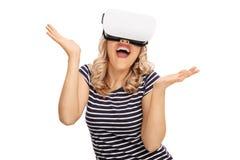 Mujer encantada que mira en gafas de un VR Imagen de archivo libre de regalías