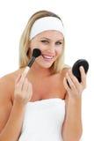 Mujer encantada que pone en maquillaje Imagenes de archivo