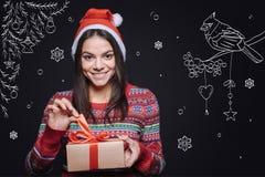 Mujer encantada que sostiene la caja con un regalo de la Navidad Fotografía de archivo libre de regalías