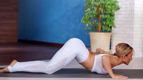 Mujer encantadora de la aptitud que goza practicando yoga en actitud de la cobra en la estera en el tiro lleno del estudio de los almacen de video
