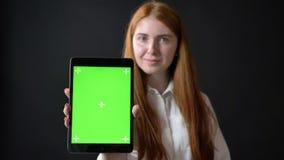 Mujer encantadora del jengibre que muestra la pantalla de la tableta con charomakey en cámara, aislada en fondo negro almacen de video