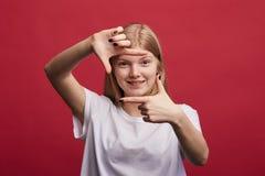 Mujer encantadora emocional feliz que hace un marco de la mano sobre fondo rojo fotos de archivo libres de regalías