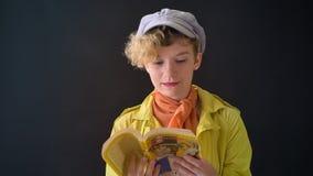 Mujer encantadora en chaqueta amarilla con el libro de lectura del pelo rizado, aislado en fondo negro, aprendizaje del estudiant metrajes