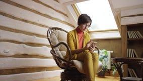 Mujer encantadora en los vidrios que enrollan newsfeed en red social en smartphone en ático almacen de video