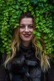 Mujer encantadora joven con el pelo largo que se coloca cerca de la pared con las hojas decorativas del día salvaje del otoño de  Imagenes de archivo
