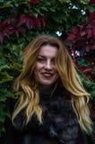 Mujer encantadora joven con el pelo largo que se coloca cerca de la pared con las hojas decorativas del día salvaje del otoño de  Fotos de archivo