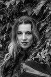 Mujer encantadora joven con el pelo largo que se coloca cerca de la pared con las hojas decorativas del día salvaje del otoño de  Imagen de archivo libre de regalías